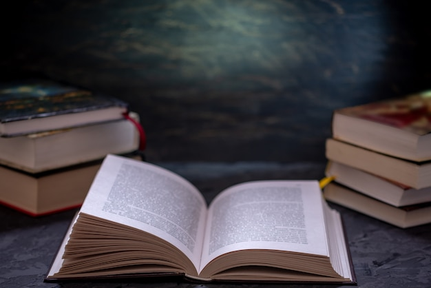 Abra o livro em uma pilha de livros sobre uma mesa. educação e leitura de livros de papel Foto Premium