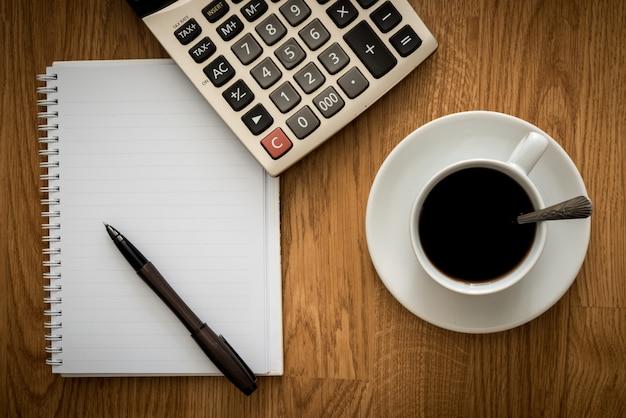 Abra um caderno branco em branco, caneta e xícara de café e calculadora Foto Premium