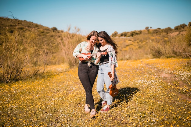 Abraçando as mulheres tocando cavaquinho Foto gratuita