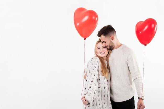Abraçando casal com balões Foto gratuita
