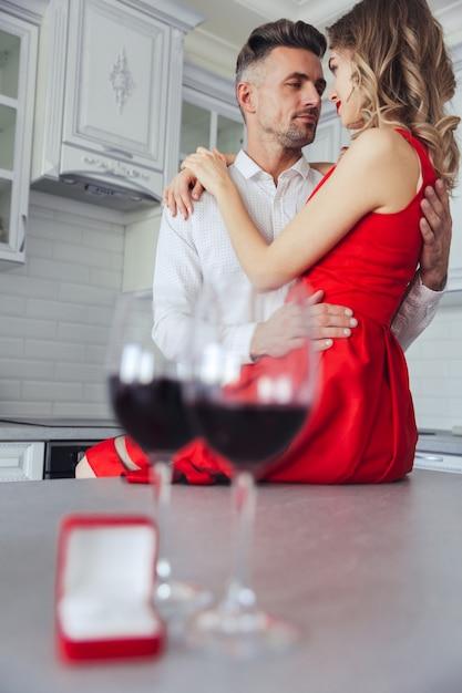 Abraçando lindo casal. copos com vinho e caixa com anel na mesa Foto gratuita