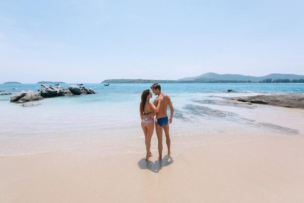 Abraçando o casal romântico, olhando o mar nas férias de praia tropical linda. paisagem do mar com barco tailandês. phuket. tailândia vista traseira. Foto Premium