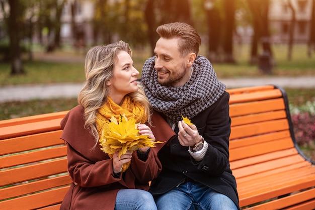 Abraçando o homem encontrou um pequeno casal feliz de folhas sentado no banco abraçado no parque vestindo casacos e lenços coletando um buquê de folhas caídas Foto Premium
