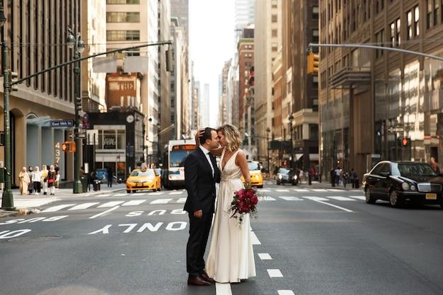 Abraçar os recém-casados fica no meio da rua na cidade de nova york Foto gratuita