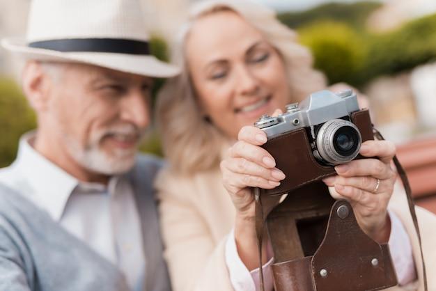 Abraços de casal velho. câmera do vintage da preensão da mulher. Foto Premium
