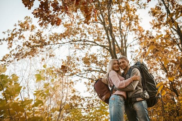 Abraços de homem e mulher em pé na floresta de outono Foto Premium