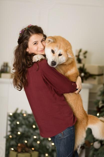 Abraços de mulher bonita, abraços com seu cachorro akita inu. no fundo de uma cômoda de árvore de natal com velas em uma sala decorada. feliz ano novo e feliz natal Foto Premium