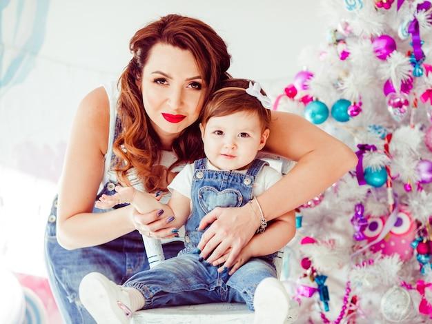 Abraços de mulher por trás, criança pequena sorrindo antes da árvore de natal Foto gratuita