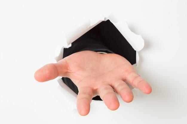 Abrir a mão estourando através do papel Foto Premium