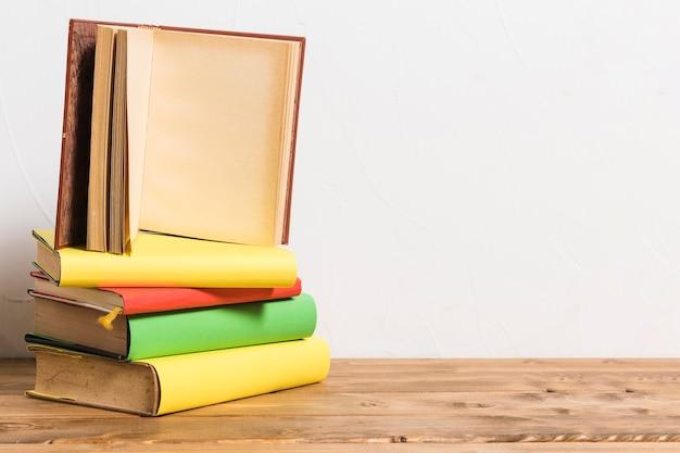 Abriu o livro vazio na pilha de livros coloridos na mesa de madeira Foto gratuita