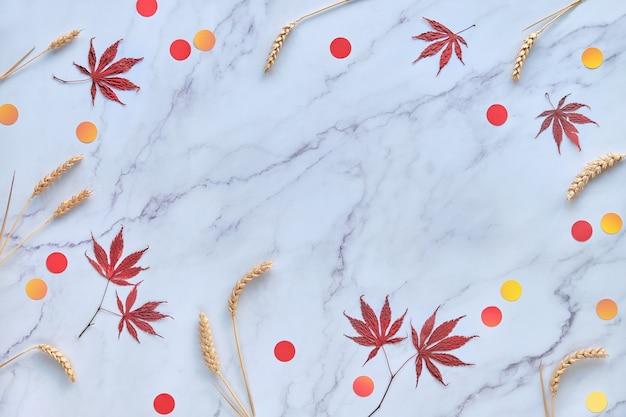 Abstrato base sazonal de outono com espigas de trigo naturais, folhas de bordo de outono e confetes de círculo de papel. Foto Premium