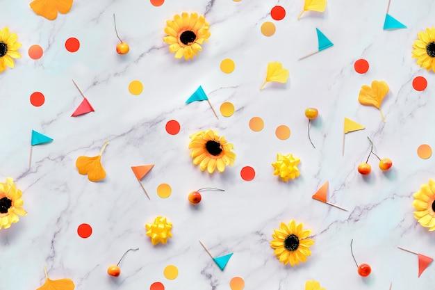 Abstrato base sazonal de outono com flores amarelas, folhas de gingko de outono, confetes de papel e sinalizadores de palito. Foto Premium