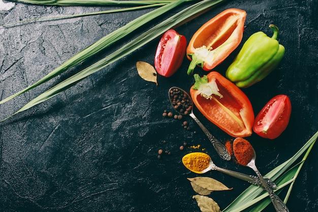 Açafrão e pimentão de pimenta preta mentem sobre um fundo escuro Foto Premium
