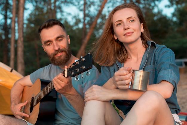 Acampamento casal curtindo a música Foto gratuita