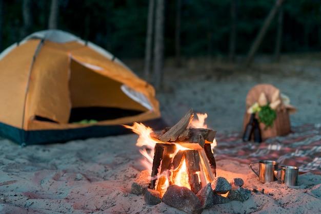 Acampamento de fogo queimando perto da tenda Foto gratuita