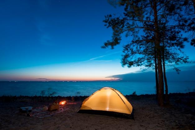 Acampar à noite no lago Foto gratuita