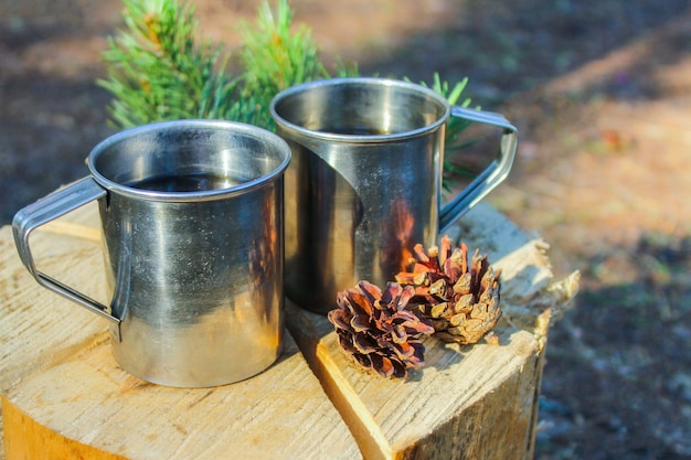 Acampar na natureza. canecas de ferro turísticas na floresta com chá de ervas cozido no fogo. recreação ao ar livre. Foto Premium