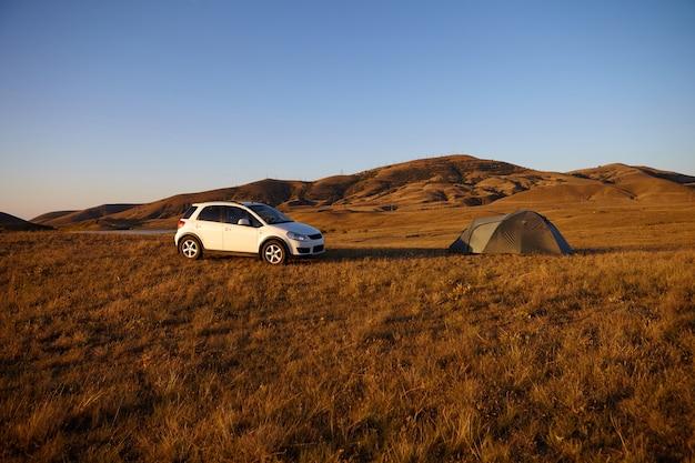 Acampar na natureza selvagem. carro moderno branco estacionado no meio do vale ao lado da barraca. turistas relaxando ao ar livre, fazendo uma pausa durante a viagem. bela paisagem de céu azul e montanhas marrons Foto gratuita