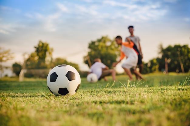 Ação esporte ao ar livre de crianças se divertindo jogando futebol Foto Premium