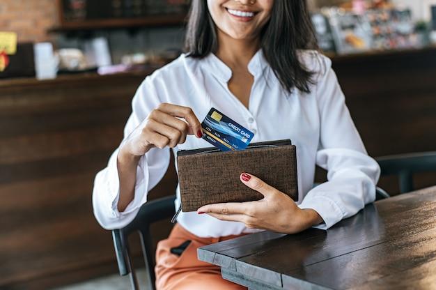 Aceitando cartões de crédito de uma bolsa marrom para pagar por mercadorias Foto gratuita