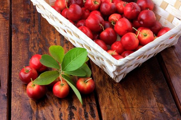 Acerola cereja cru, fresco, caixa na mesa de madeira rústica, frutas antioxidantes Foto Premium