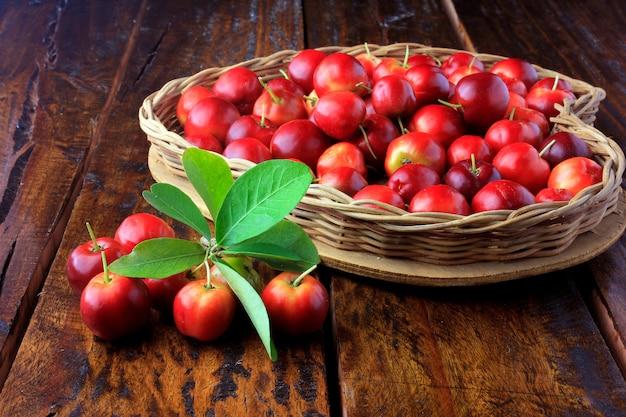 Acerola cereja crua, fresca, na cesta com forma de coração na mesa de madeira rústica Foto Premium