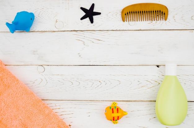 Acessórios de banho de bebê vista superior com fundo de madeira Foto gratuita