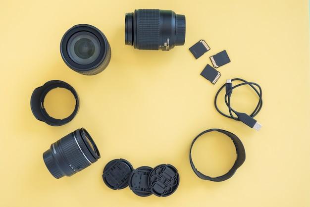 Acessórios de câmera digital profissional dispostos em círculo sobre fundo amarelo Foto gratuita