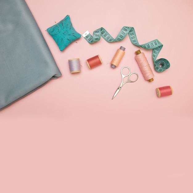 Acessórios de costura e tecido em um fundo rosa. Foto Premium