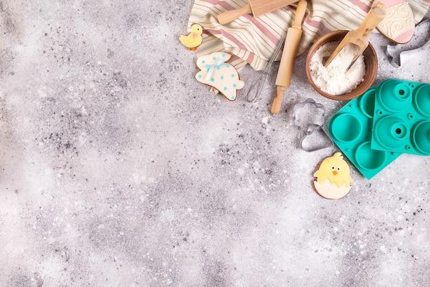 Acessórios de cozimento no fundo de pedra com farinha e biscoitos vitrificados de páscoa Foto Premium