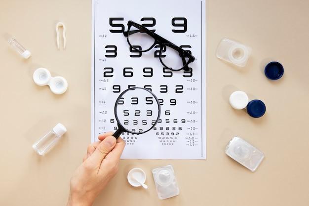 Acessórios de cuidados dos olhos em fundo bege com tabela de números Foto gratuita
