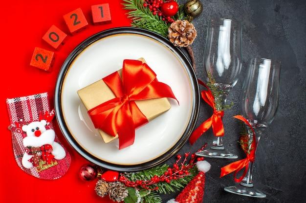 Acessórios de decoração de pratos de jantar ramos de abeto xsmas meias números num guardanapo vermelho e taças de vidro no fundo escuro Foto gratuita