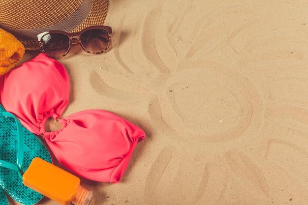 Acessórios de férias no fundo da praia de areia Foto Premium