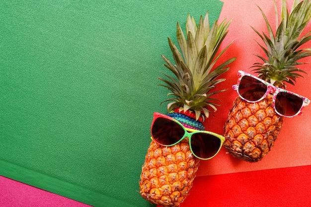 Acessórios de moda de abacaxi hipster e frutas em fundo colorido Foto Premium