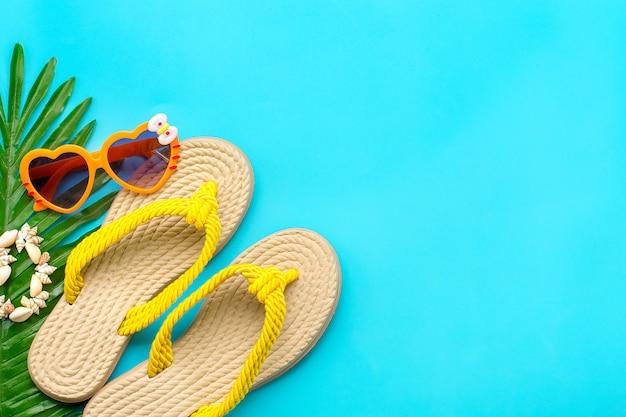 Acessórios de natação - protetor solar, óculos em forma de coração, chinelo amarelo, palma, pulseira de conchas isolada Foto Premium