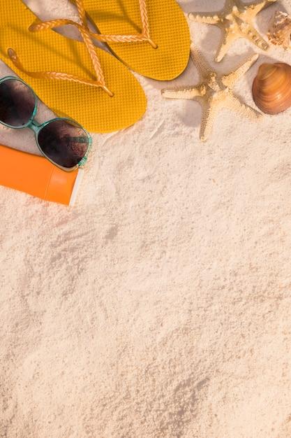 Acessórios de praia feminino na areia Foto gratuita