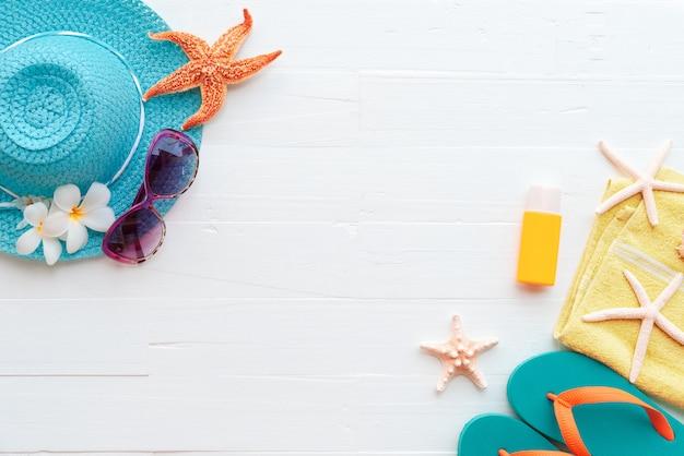 Acessórios de praia no fundo de madeira pastel azul brilhante para as férias de verão Foto Premium