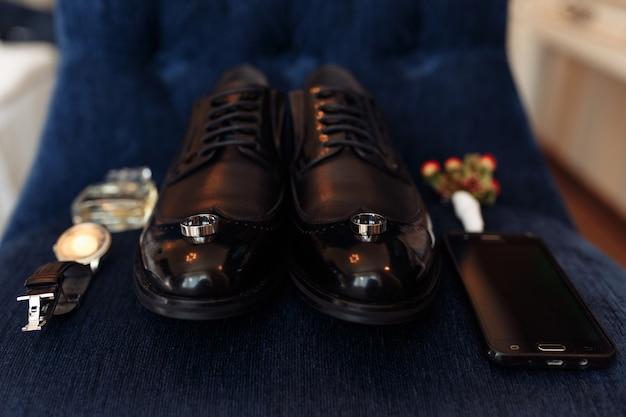 Acessórios de um noivo: sapatos, boutonniere, telefone, parfum e relógio Foto gratuita