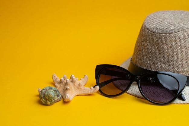 Acessórios de verão, conchas, chapéu e óculos de sol na superfície amarela. Foto Premium