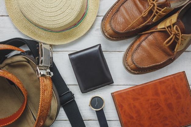 Acessórios de vista superior para viajar com o conceito de vestuário do homem. carteira em fundo de madeira. revestimento, bolsa, chapéu, caderno e sapato na mesa de madeira branca. Foto gratuita