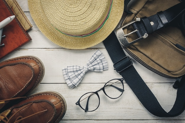 Acessórios de vista superior para viajar com o conceito de vestuário do homem. laço de arco em fundo de madeira. relógio, óculos, saco, chapéu, avião, mapa na mesa de madeira branca. Foto gratuita
