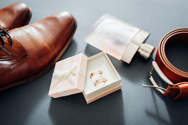 Acessórios do dia do casamento do noivo. sapatos de couro marrom, cinto, perfume, anéis de ouro Foto Premium
