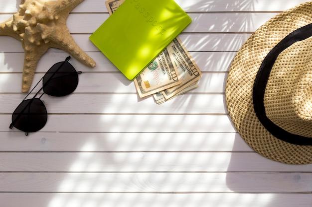 Acessórios do viajante - passaporte com dólares americanos do dinheiro do dinheiro, chapéu, sombra de ramos tropical da folha de palmeira. Foto Premium