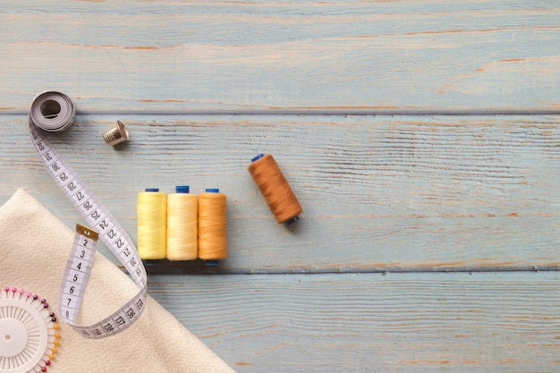 Acessórios e tela sewing em um fundo azul. tecido, linhas de costura, agulha e centímetro de costura. vista superior, flatlay, copyspace Foto Premium
