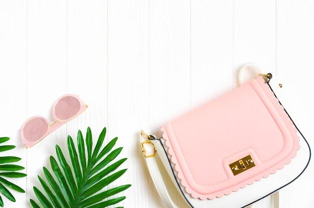 Acessórios femininos - bolsa branca - rosa, rosa da moda - óculos coloridos com óculos de espelho, folhas de palmeira em fundo branco de madeira Foto Premium