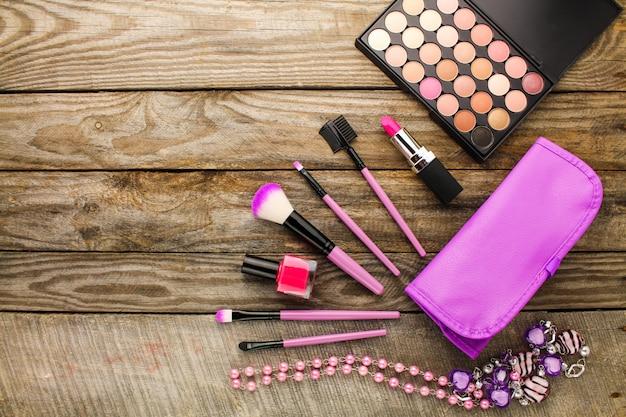 Acessórios femininos: bolsa de cosmética, pincéis de maquiagem, colar, unha polonês, batom. Foto Premium