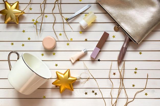 Acessórios femininos em saco cosmético, rímel, cremes, loções, batom e copo no natal de madeira com estrelas douradas. Foto Premium