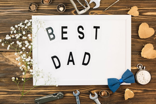 Acessórios masculinos perto de moldura com melhor pai título e planta Foto gratuita