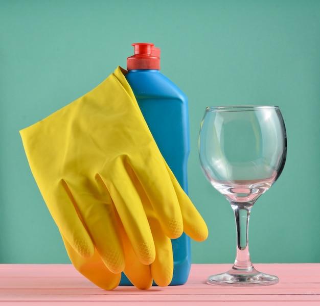 Acessórios para lavar louça e limpeza de casas. lavar pratos. frasco de detergente, vidro e luvas de borracha amarela Foto Premium