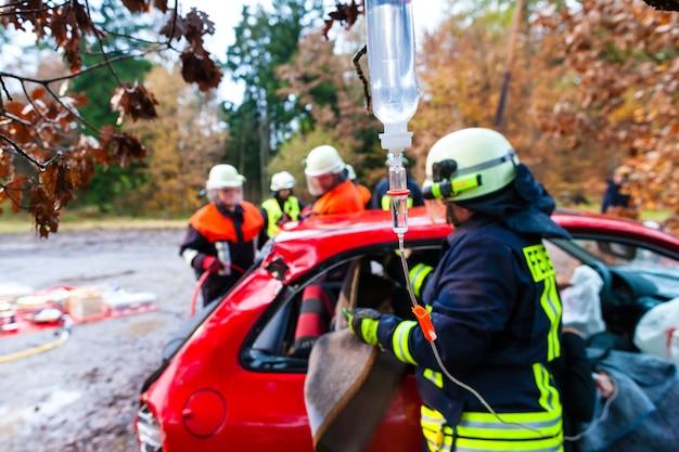 Acidente - resgate de brigada de incêndio vítima de um acidente de carro Foto Premium